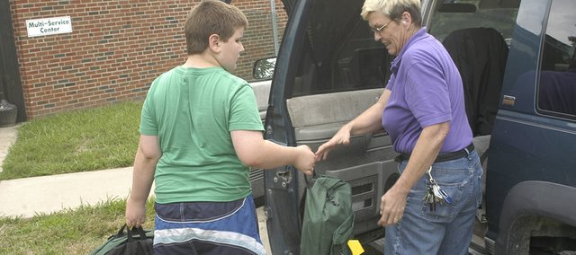 Caleb Miller, 11, De Soto helps LisaDawn McCabe, rural Olathe, load backpacks into her car Thursday. McCabe picked up seven backpacks filled with school supplies for her children at the De Soto Multi-Service Center.