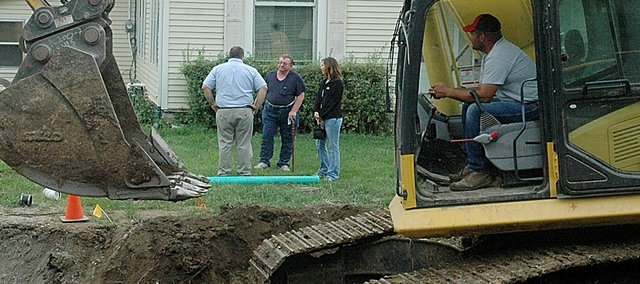 Baldwin City Administrator Jeff Dingman, back to camera, listens to Bob Bigsby's complaints regarding the Sixth Street sewer project as Bigsby's niece Kalli Keen looks on Thursday morning. Bigsby spent an hour in a hole to protest the project and halt work until Dingman arrived.