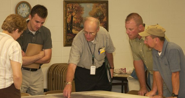 Dennis Haag of the engineering firm Burns and McDonald points to a feature on an aerial map of the Rieke Lake site west of De Soto at a June worksho in the De Soto Senior Center meant to get public comment on how the site should be developed as a Johnson County Parks and Recreation District regional park. A second workshop at which a preliminary master plan will be revealed will start at 6 p.m. Monday at the Senior Center, 32905 W. 84th St.