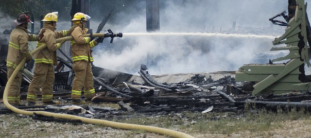Firefighters finish putting out a fire that destroyed a detached garage and workshop on Monday,  just south of Kansas Highway 32 and County Road 1. There were no injuries reported. The cause of the fire is still under investigation.