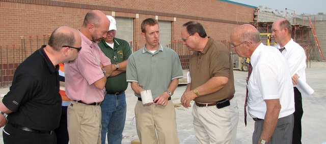 Gordon Kimble, (middle) of Horst, Terrill and Karst Architects, holds a core sample of the concrete floor slab of Glenwood Ridge Elementary School&#39;s new addition Monday while school board members look on. HTK revealed that the concrete slab may have been completed below par.