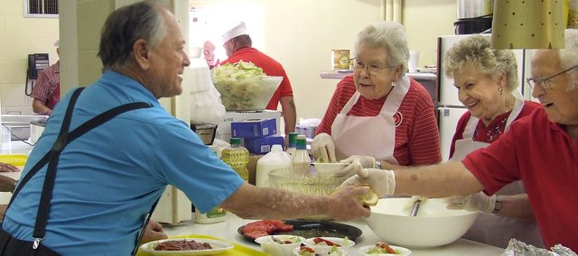 Billy Allen, front, and Glenna Reynolds, make their way through the food line Friday at the Senior Center's spaghetti dinner. The event raised $1,500 for three local scholarships.