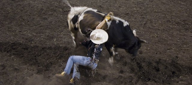 A bull rider gets knocked off before he finishes his eight-second run at Thursday night's rodeo at the Leavenworth County Fair in Tonganoxie.