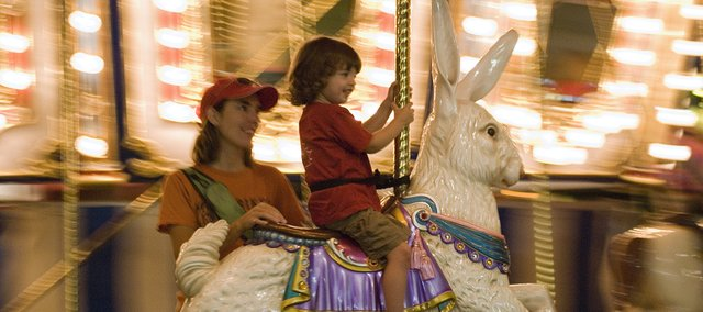 Dakota Jackson, 2, and her mother Nicole ride the carousel at the Leavenworth County Fair Friday night.