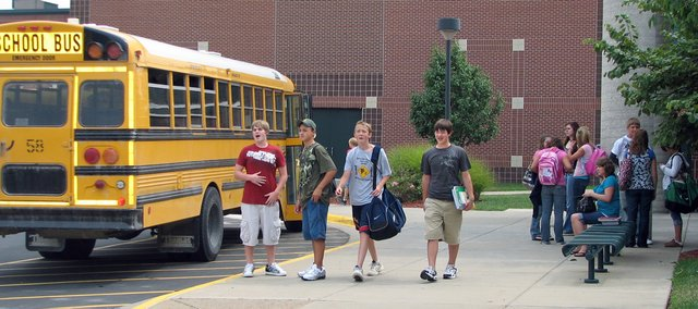 Basehor-Linwood High School students (above) get ready to get on the bus after the conclusion of the school day Friday afternoon. Students exit the school building Friday, which was the first day of school for 10th- through 12th-graders. The first day of school for kindergarten through ninth grade was Thursday. District officials report preliminary increases in residential enrollment.