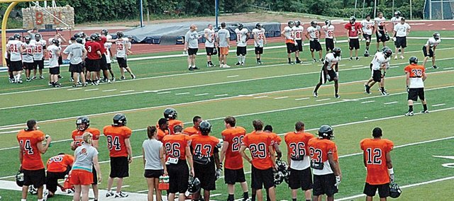 Members of the Baker University football team run through a 7-on-7 passing drill at practice Tuesday afternoon at Liston Stadium. The Wildcats begin the season with two road games before returning to Liston for their home opener Sept. 20.
