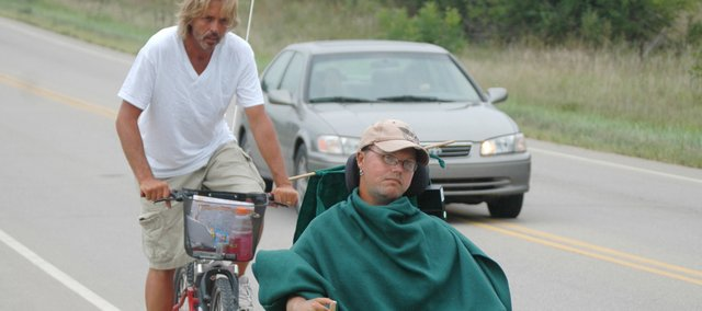 Matt Eddy and his caretaker, Ron Steenbruggen, head south on 24-40 near Tonganoxie's city limits about midday on Wednesday. The two left Massachusetts on June 30 and are on their way to Long Beach, Calif. As they traverse the country, they are spreading the word about their nonprofit organization, Matt's Place.