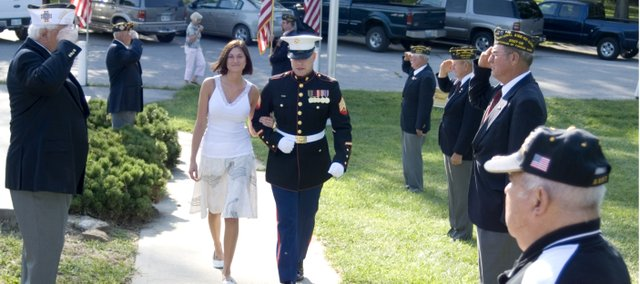 Sgt. Tyler Robinson and his girlfriend, Victoria Wilson, walk among Tonganoxie VFW Post 9271 saluting Robinson. The Tonganoxie High School alumnus was welcomed home after serving in Iraq.