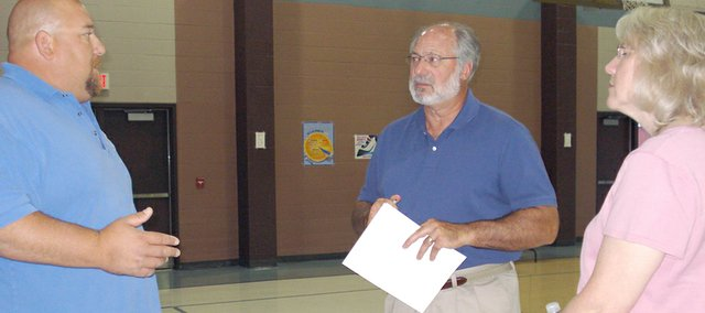 Basehor City Superintendent Gene Myracle (left) talks to Cedar Lakes residents David and Jennifer Espenshade during the Cedar Lakes open house Monday night at Glenwood Ridge Elementary School. The city of Basehor plans to annex the subdivision and hosted the event to disperse information and answer questions.