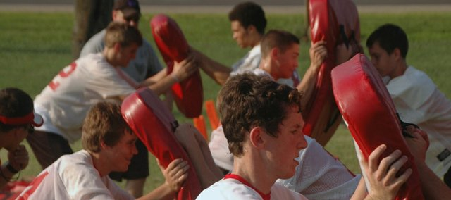 Members of the Tonganoxie High football team go through blocking drills.