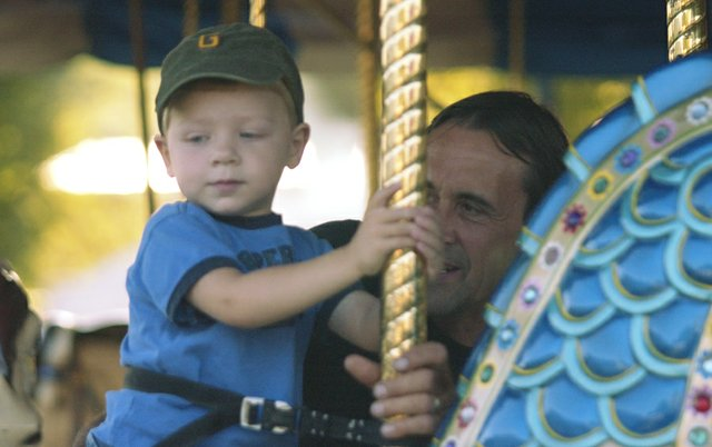 John Lobner accompanies his 2-year-old grandson Blake Weese on his second carnival ride Friday at the De Soto Days Festival.