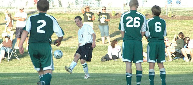 Brett Hevel attempts to bend the ball through Basehor defenders on a free kick Friday. De Soto controlled most of the match and won, 1-0, in its opener.