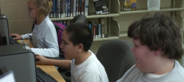 Thomas Hart, 11, Manuel Avila, 11 and Care VanDusen work and play Tuesday on computer in the De Soto Library. Recent figures show more adults are joining children at the library.