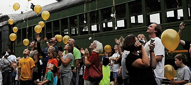 Participants in Saturday's train ride and balloon launch let the yellow balloons go in honor of those fighting childhood cancer. About 200 people took part in the event that started at Midland Railway.
