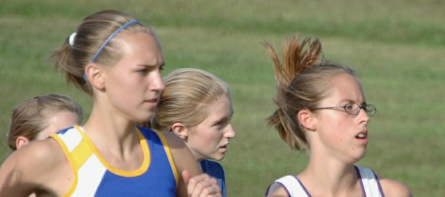 Gelia Gardner, far right, senior runner for McLouth High, runs the final home race of her prep career on Thursday for the Bulldogs. Gardner finished the 4K course 44th with a time of 21:24.