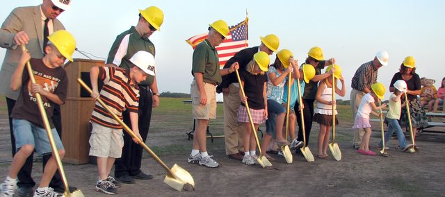 Basehor-Linwood School District elementary students (from left) Dalton Lindelof, Parker Rusk, Rachel Tindell, Katherine Karrick, Brock Gilliam, Payton Rusk, Gabby Coleman and Catie Coleman with the help of school and construction officials turn the first shovels of soil Monday evening at site of the future Basehor Intermediate School. The school, located southeast of the 155th and Hickory streets intersection, is expected to be completed by winter 2009.