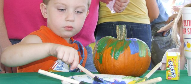 Triston Owen, 4, of Turner, paints a pumpkin Saturday during Edwardsville AutumnFest.