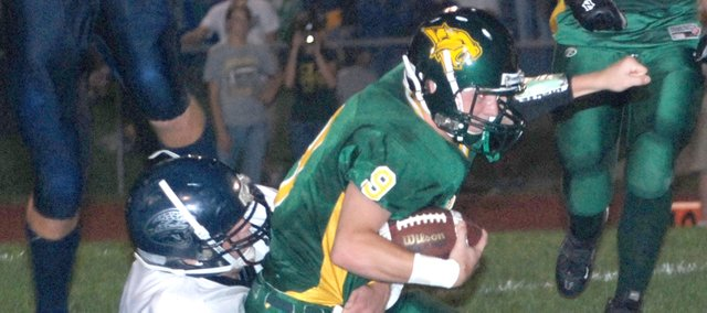 Basehor-Linwood quarterback Brandon Leppke is dragged down by Mill Valley's Slobodan Kanatzar.