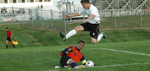 Paul Oswald leaps over Eudora goalkeeper Ben Miller last Thursday at De Soto.