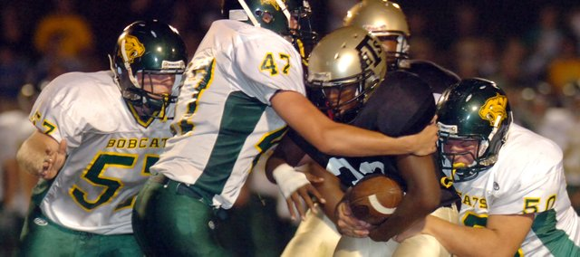 The Basehor defense of Adam Schelert (57), Clint Schirbaum (47) and Jon Shewmon (50) made it tough for Turner running back Rashon Johnson to get yardage Friday night in the first half.