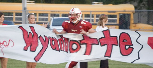 "Tonganoxie High senior lineman Jamie Everett runs through the ""Whoop Wyandotte"" sign before the Chieftains' game on Friday night at Beatty Field. THS did just that, defeating WHS, 34-8."