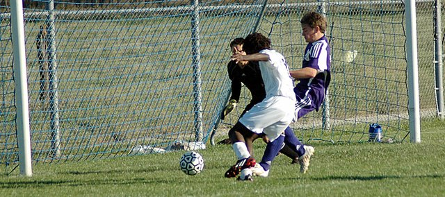 Baldwin High School freshman Shawn Berndt, center, outruns a Spring Hill defender and kicks the ball past the Broncos' goalie Tuesday. Berndt scored one of Baldwin's three goals as the Bulldogs beat Spring Hill 3-1.