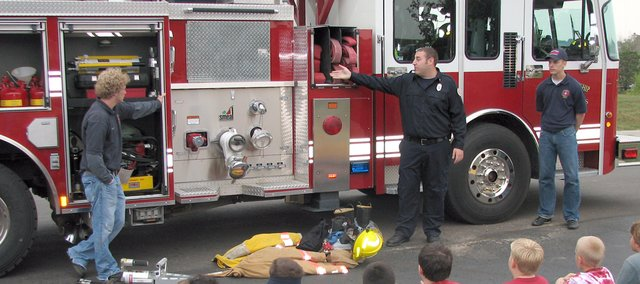 Fairmount Township firefighter Dave Mellen (middle) explains the different tools on the station's ladder truck to a group of Glenwood Ridge Elementary School students Monday afternoon while cadets Austin Call (left) and Cole DeRuse look on. The firefighters have been visiting different groups of children this week in recognition of Fire Safety Month.
