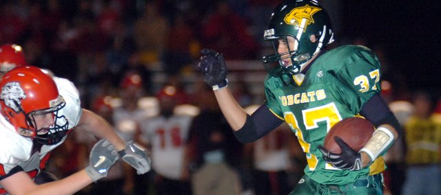 Basehor-Linwood senior running back Zachery Smith (37) tries to find some open space around the Lansing defense for yards in the fourth quarter Friday night. The Lions mauled the Bobcats 43-8.