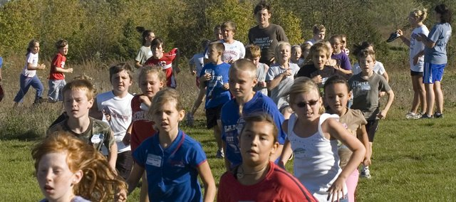 Tonganoxie Elementary School students run the Tonganoxie cross country course on Wednesday, Oct. 8 with Tonganoxie High runner Matt Titterington, one of the course guides for the annual Kids Cross Country race.
