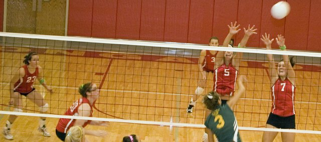 Tonganoxie High's Molly O' Hagan and Megan Puhr rise for a block as teammates Chrissie Jeannin and Maggie Franuik look on.