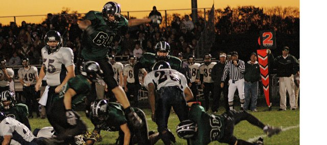 Aaron Donnell takes down a St. James runner Friday night at De Soto as Jake Radell (60) leaps to help. The Wildcats won their third consecutive game by defeating St. James, 28-7, Friday night. The Wildcats are 3-4 and 1-0 in district play.