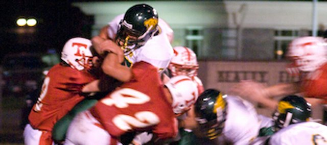The Tonganoxie High defense, led by junior linebacker Jeremie Maus, tries to slow down the Basehor-Linwood offense on Friday night at Beatty Field. The Chieftains didn't stop the Bobcats often enough, and fell, 38-15, in their district opener.