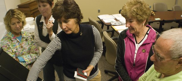 Janet Klasinski, Leavenworth County deputy clerk, shows poll workers Jeanie Williams, Tonganoxie, Debbie Breuer, Basehor, Pat Young, Basehor, and Steve young, Basehor, how to use the electronic voting machines for the Nov. 4 election.