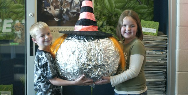 Starside second-graders Tanner Cadwallader and Katelyn Drennon team up to hold Bob the Ball,who has grown to his present size since Sept. 1 by devouring De Soto's scrap aluminum foil.