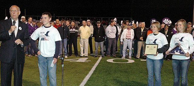 Sen. Pat Roberts, left, addresses the crowd at Friday night's veterans salute at the Baldwin High School football game. Next to him is BHS sophomore Colin Thomas, who spearheaded the event. The veterans are standing behind them. Standing to the right are BHS sophomore Michaela Krysztof and junior Lauren Barnes.