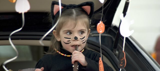 A Tonganoxie girl takes a bite out of some candy during Halloween last year.