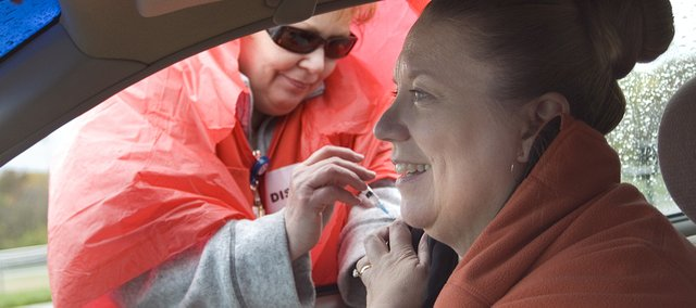 Deborah Whitney, of St. John's Hospital, gives Cathy Adams, Leavenworth, a flu vaccination during an October 2008 drive-through flu shot clinic in Leavenworth.