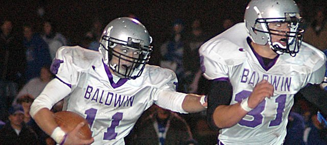Baldwin High School senior Sam Beecher  (No. 11) follows sophomore Landon Ausherman during a run Friday night. Beecher and Ausherman combined to score all five touchdowns in the Bulldogs' 35-28 victory. Junior Camdon Schwartz caught a touchdown pass from Beecher.