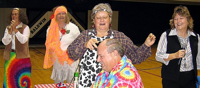 Baldwin Junior High School Assistant Principal Joe Gresnick gets his head shaved Friday morning after BJHS reached the Standard of Excellence marks on all of the 2008 Kansas State Assessments. Doing the honor is teacher Sandy Bayha, while Principal Connie Wright, right, and social worker Laura McCall look on.