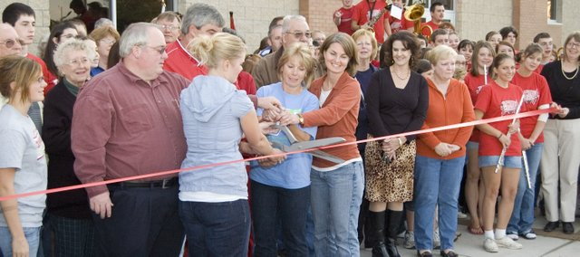 Pam Jeannin, with help from fellow Tonganoxie residents, cuts the ribbon at a dedication ceremony Thursday at    the Chieftain Remembrance Walk outside Tonganoxie High School. Left of Jeannin, also in light blue, is Kelly Frantz, who is Jeannin's daughter. Frantz's husband, Cpl. Lucas Frantz, was killed in 2005 while serving in Iraq. The courtyard grew from an idea to honor Frantz and will recognize living and deceased members of the community for years to come.