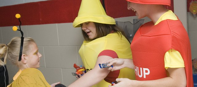 Bumblebee Mia Bond gets candy from Emily Jefferies, mustard, and Bret Koch, ketchup, at the Tonganoxie Elementary School during Friday night&#39;s spooktakular Halloween celebration. Hundreds of local residents went door to door visiting downtown business trick-or-treating. 