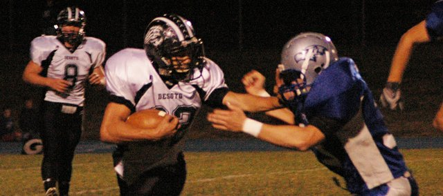 Mark England stiff arms a Perry-Lecompton defender Tuesday night at Perry. The Wildcats lost to the Kaws 23-0 in the first round of the playoffs.