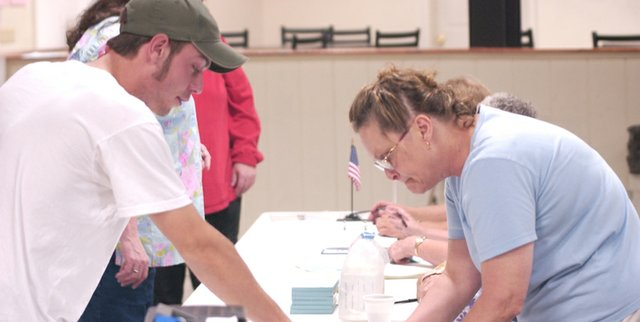 With the help of supervising judge Christine Peterson, first-time voter Jed Sides looks for his name on the voter registration books Tuesday afternoon at the De Soto Precinct 1 polling site at De Soto VFW Post 6654.