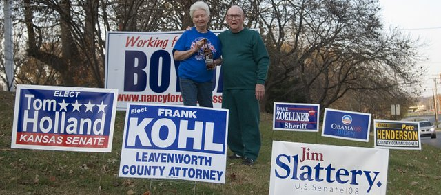 Lifelong Democrats Jackie Wolfe and her husband Jack stand near all of their political yard signs Tuesday evening. Jack, who said he was going to vote a straight ticket for all the Democratic candidates, first voted in 1948 when Harry Truman defeated Thomas Dewey. Jackie is holding a souvenir inauguration bottle Jack found on Fourth Street in 1953 after Dwight Eisenhower defeated Adlai Stevenson in the 1952 general election.