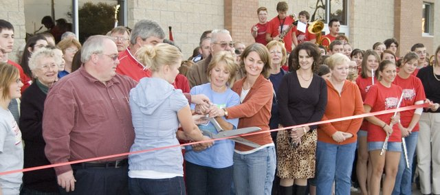 Pam Jeannin, with help from fellow Tonganoxie residents, cuts the ribbon at a dedication ceremony Thursday at the Chieftain Remembrance Walk outside Tonganoxie High School. Left of Jeannin is Kelly Frantz, who is Jeannin's daughter. Frantz's husband, Cpl. Lucas Frantz, was killed in 2005 while serving in Iraq. The courtyard grew from an idea to honor Frantz and will recognize living and deceased members of the community for years to come.