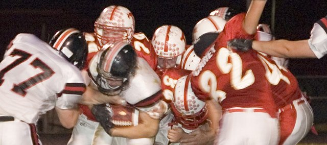 Tonganoxie High seniors Clint Kissinger (79) and Boomer Carey (32), along with their Chieftain teammates, converge on a Bishop Ward ball carrier on Thursday night at Beatty Field. The Chieftains were led this season by a small, seven-player senior class.