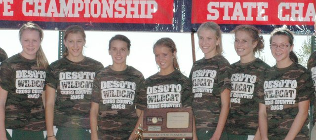 The De Soto girls cross country team shows off its second-place state trophy at Wamego last Saturday. The girls finished in second-place last year as well.