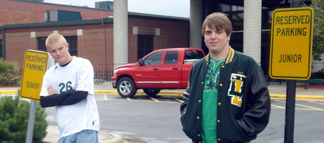 Basehor-Linwood High School senior Josh Keopke (left) and junior Zach Ross stand by their respected reserved parking spots in the teacher's parking lot at the high school. The students recently won a fundraising drawing allowing them front-row parking for a week.