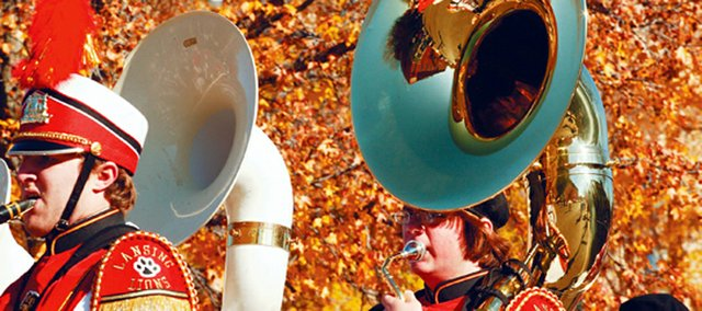 Members of the Lansing High School marching band participate in the Leavenworth Veterans Day Parade under a canopy of fall leaves.