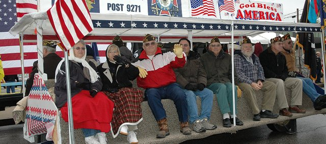 Members of Tonganoxie VFW Post 9271 wave to the crowd at Tuesday's Veterans Day Parade in Leavenworth. The event, in its 89th year, is the oldest in the nation and largest west of the Mississippi River.